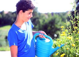 Ein Junge gießt Blumen mit einer Gießkanne.