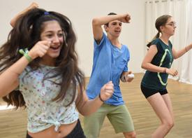 Drei Jugendliche tanzen und lächeln in einem Trainingsraum.