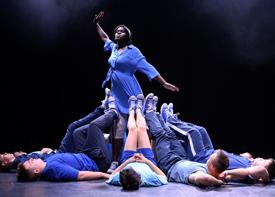 Eine junge Frau steht in der Mitte einer Gruppe von Tänzern, die am Boden liegt. Sie reckt beim Tanzen einen Arm in die Höhe.