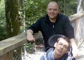 Ein Junge im Rollstuhl und seine Begleitung stehen im Wald auf einer Holzbrücke.