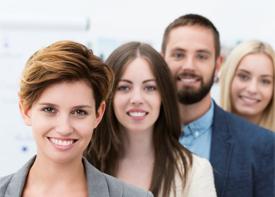 Vier Mitarbeiter einer Firma lächeln in die Kamera.