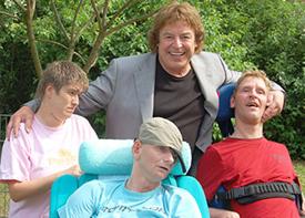 Der Sänger Tony Marshall und drei weitere Personen stehen in einem Garten. Der Sänger lächelt in die Kamera.
