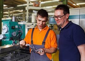 Ein Mann in einer Arbeitshose und sein Vorgesetzter stehen neben einer Maschine und begutachen ein Produkt.