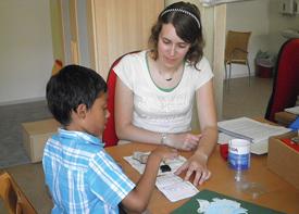 Ein Junge und eine Therapeutin sitzen an einem Tisch und sind ins Stempeln vertieft.