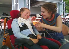 Ein Mädchen im Rollstuhl und ihre Assistenzkraft sitzen vor einem Café und essen Eis.