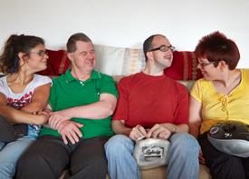 Vier Erwachsene sitzen entspannt auf einem Sofa und unterhalten sich.