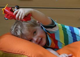 Ein kleiner Junge liegt auf einem Kissen und spielt mit einem Flugzeug.