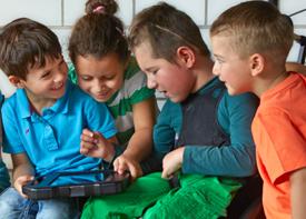Vier Kinder sitzen um einen Talker und unterhalten sich.