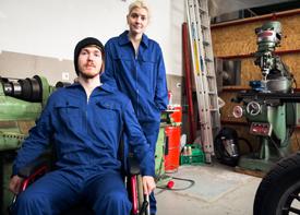 Ein junger Mann im Rollstuhl und eine junge Frau stehen in Arbeitskleidung in einer Werkstatt.