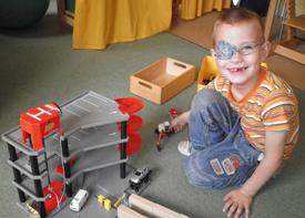 Ein Junge spielt auf dem Fußboden mit einer Autogarage.