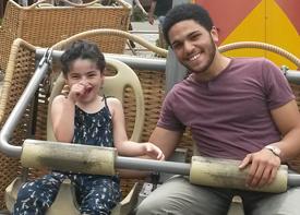 Ein Mädchen und eine Assistenzkraft sitzen im Sitz eines Fahrgeschäfts im Freizeitpark Tripsdrill.