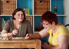 Zwei Frauen sitzen an einem Tisch und spielen ein Gesellschaftsspiel.