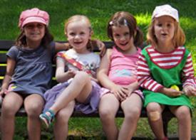 Vier Kinder sitzen auf einer Bank.