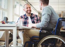Zwei Männer, einer davon im Rollstuhl, sitzen an einem Tisch und unterhalten sich.