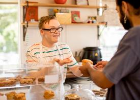 Ein Mitarbeiter eines Cafés verkauft einem Kunden Gebäck.