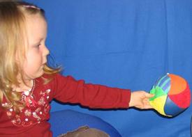 Ein kleines Mädchen spielt mit einem Ball.