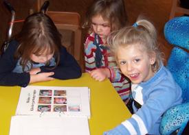 Drei kleine Mädchen sitzen an einem Tisch und gucken sich einen Ordner mit Fotos an.