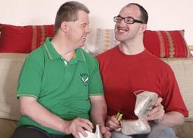 Zwei Männer sitzen auf einem Sofa und unterhalten sich.