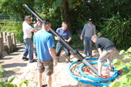 Sechs Personen richten zusammen einen Kletterbaum auf.