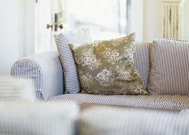 Ein Sofa mit Kissen in einem Wohnzimmer.