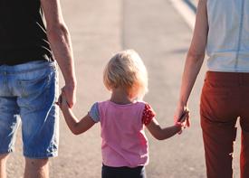 Ein Kleinkind geht Hand in Hand mit zwei Erwachsenen spazieren.