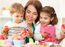 Eine Erzieherin sitzt mit zwei kleinen Kindern an einem Tisch. Sie bemalen Ostereier.