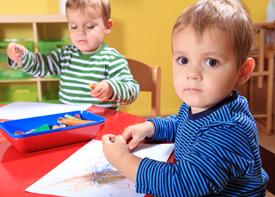 Zwei Kleinkinder sitzen an einem Tisch und malen mit Stiften.