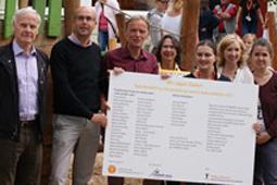 Sieben Personen halten eine Tafel, auf der die Namen der Spender für die Kita Rosengarten aufgelistet sind.