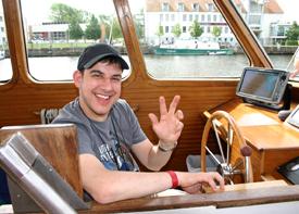 Ein junger Mann mit Schirmmütze sitzt am Steuer eines großen Motorboots und winkt. Im Hinergrund ist eine Anlegestelle zu sehen.