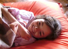 Ein Mädchen liegt auf einem Stützkissen unter einer Decke und lacht.