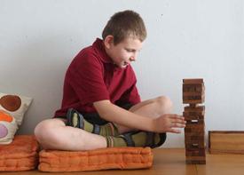 Ein Junge sitzt auf dem Fußboden und baut einen Turm aus flachen Holzklötzen.