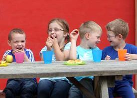 Vier Kinder sitzen draußen an einem Tisch. Sie essen und trinken und lachen miteinander.