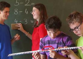 Vier Schüler stehen vor einer Tafel und rechnen etwas aus. Zwei von ihnen beugen sich über ein Lineal.