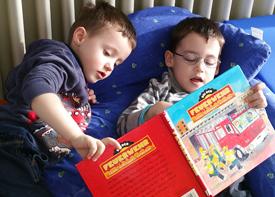 Zwei kleine Kinder liegen auf einem Kissen und sehen sich ein Bilderbuch über die Feuerwehr an.