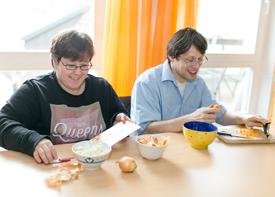 Ein junger Mann und eine junge Frau sitzen am Küchentisch und bereiten das Essen zu. Sie schneidet Zwiebeln, er Karotten.