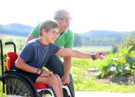 Ein Junge im Rollstuhl spielt Boule. Er zielt mit einer Boule-Kugel. Ein Assistent steht neben ihm. Sie sind draußen im Grünen, es ist schönes Wetter.