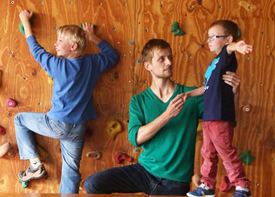 Ein Therapeut ist mit zwei Jungen in einer Turnhalle. Er hilft dem Jüngeren beim Balancieren. Der Ältere klettert eine Kletterwand hoch.