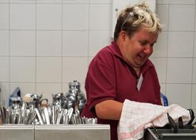 Eine Angestellte steht in einer Großküche und trocknet Besteck ab.