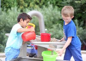 Zwei Jungen spielen in einem Wasser-Spielbereich mit Eimern, Wasser und Sand.