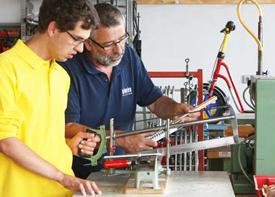 Ein junger Mann arbeiten gemeinsam mit einem älteren Kollegen in einer Werkstatt  an einer Säge.