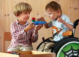 Zwei kleine Jungs bauen zusammen mit Duplo-Steinen. Einer von Ihnen sitzt im Rollstuhl.