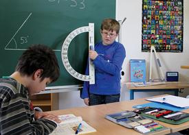 Zwei Jungen lösen in einem Klassenzimmer Aufgaben. Einer sitzt am Tisch, einer steht an der Tafel.