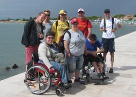 Eine Reisegruppe mit acht Erwachsenen steht an einem Hafenbecken.