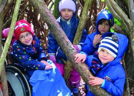 Vier Kinder mit Jacken und Mützen stehen in einem Weidenhäuschen.