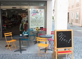 """Am Eingang von Tonis Ladencafé stehen drei kleine Kaffee-Tische mit mehreren Stühlen. Auf einem Klappschild steht """"Offen!"""""""