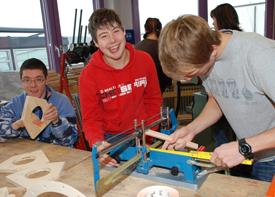 Eine Schulklasse ist im Werkraum mit Holzsägen beschäftigt. Zwei Jungen stehen an einer Säge. Einer misst etwas aus, der andere lacht in die Kamera.