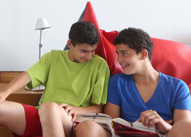 Zwei Jugendliche sitzen in einem Sitzsack und schlagen etwas in einem dicken Buch nach.