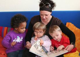 Eine Erzieherin sitzt mit drei Kleinkindern auf einem Sofa und liest ihnen aus einem Bilderbuch vor.