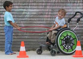 Zwei Jungen spielen mit Verkehrshütchen und einem Reifen. Einer der beiden sitzt im Rollstuhl.