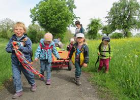 Acht Kinder sind mit einer Erzieherin auf einem Feldweg unterwegs. Zwei Kinder ziehen einen Bollerwagen mit dem Gepäck.